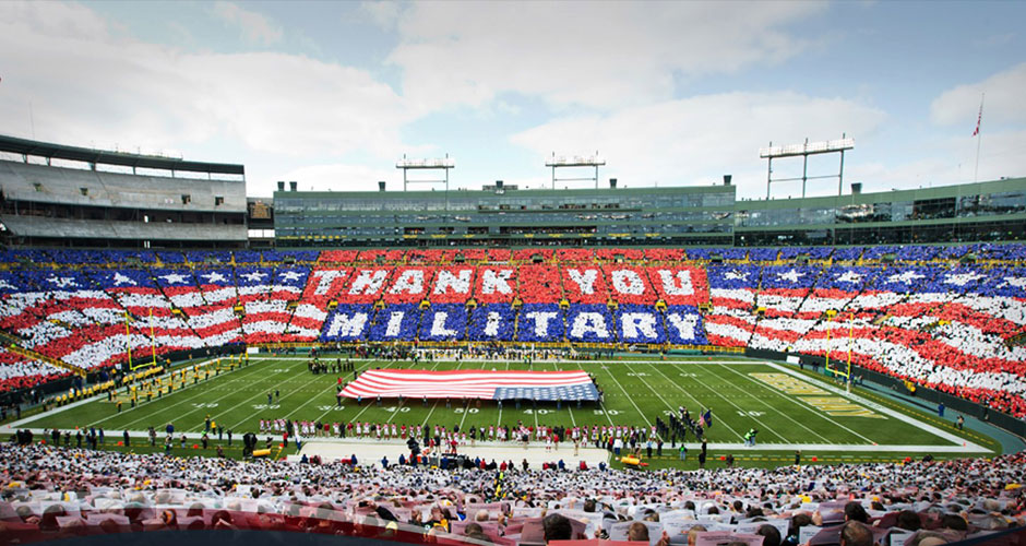Image of a football stadium doing a card stunt thanking the military.